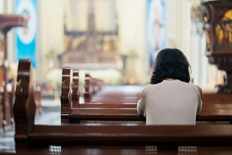 A woman sits kneeling in prayer inside a Catholic church.