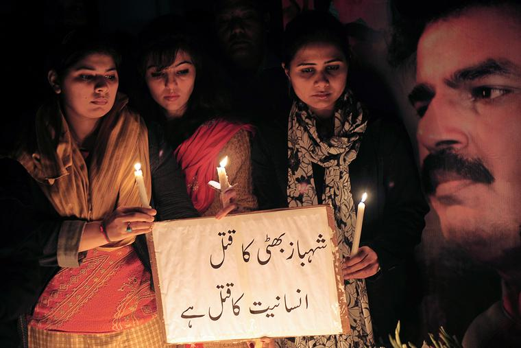 """Pakistani civil rights activists gather during a ceremony on the site of the attack on slain Pakistani minority affairs minister Shahbaz Bhatti in Islamabad on March 3, 2011. Pakistan announced three days of national mourning and vowed """"fool-proof"""" security after a Christian government minister who decried Islamic blasphemy laws was gunned down."""