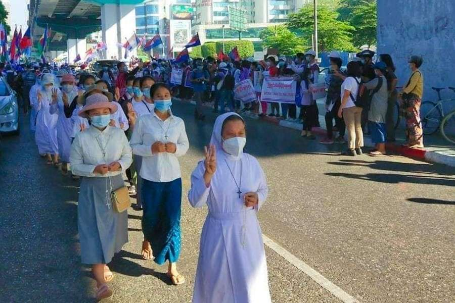 "Burmese nuns marching holding the pro-democracy ""three-finger salute"""