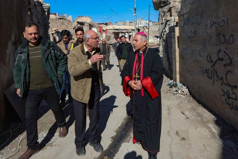 The Chaldean Catholic Archbishop of Mosul Najeeb Michaeer (R) tours the old part of the northern city of Mosul, to follow the progress of restoration works there, on February 3, 2021. From Mosul's rubble-strewn streets to ancient churches at Karamlesh badly damaged by the Islamic State group, Archbishop Najeeb Michaeel is preparing for the first-ever papal visit to Iraq.