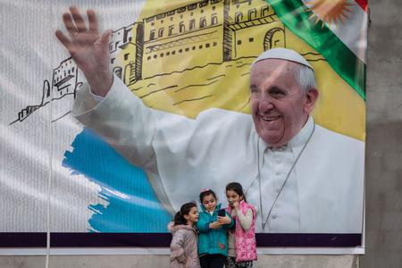 Young girls take a selfie in front of a poster promoting the upcoming trip of Pope Francis on March 4, 2021 in Erbil, Iraq. On March 5, Pope Francis will start the historic first ever papal visit to Iraq. In his first foreign trip since the start of the pandemic Pope Francis will visit Baghdad, Najaf, Erbil and the cities of Qaraqosh and Mosul, which were heavily destroyed by ISIS.