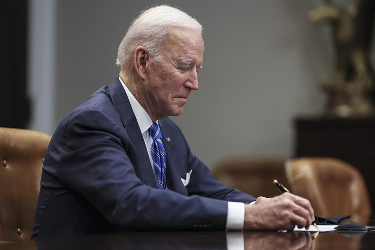 President Joe Biden takes notes during a virtual call in the Roosevelt Room of the White House on Thursday
