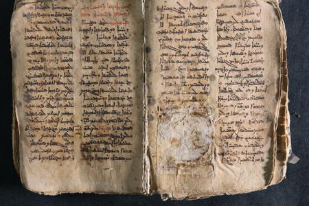 A historic Aramaic prayer manuscript restored after descration by the Islamic State. During his Iraq visit, Pope Francis returned the manuscript to the Catholic church where it was once held.