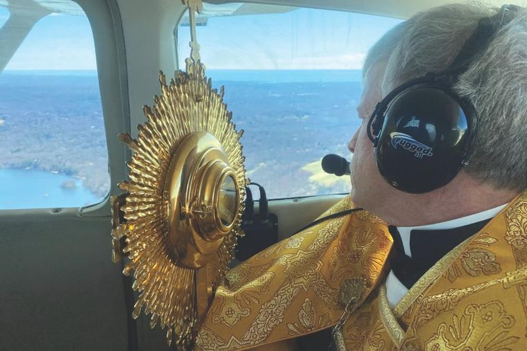 Father Brian Gannon, pastor of St. Theresa Church, flies across the Diocese of Bridgeport, Connecticut, holding a monstrance as he offers a Eucharistic blessing to local Catholics.