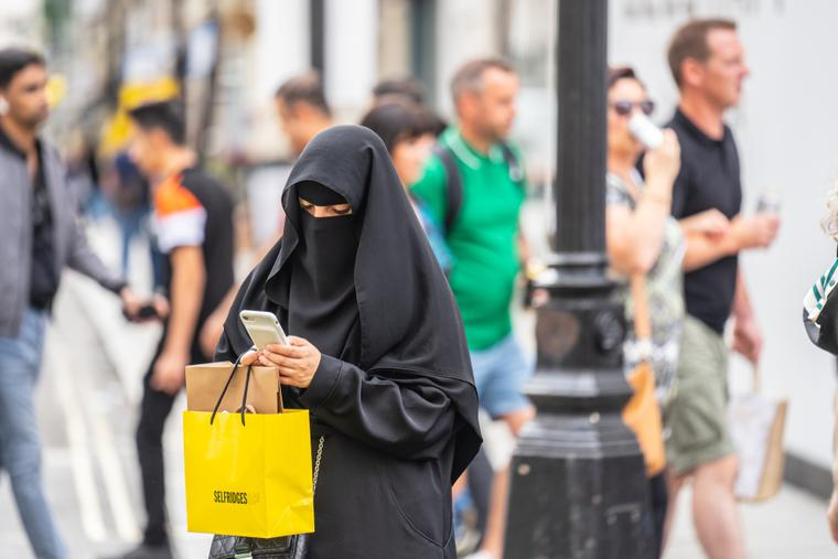 A woman wearing a niqab, using mobile phone while shopping.