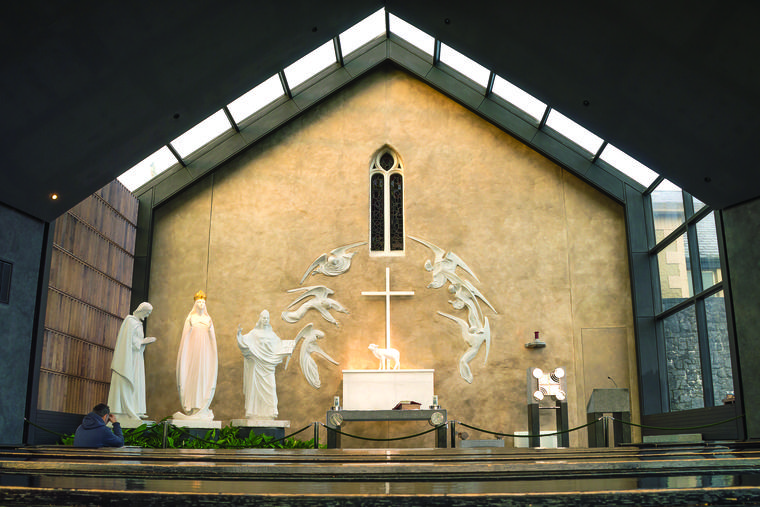 The apparition gable with statues in the Knock Shrine in Ireland highlights the 1879 apparition of Our Lady, St. Joseph (far left), St. John and the Lamb of God on the altar with angels.