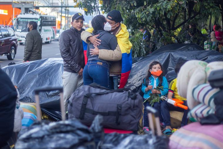 Several immigrants from Venezuela with suitcases on the street waiting to return to their country.