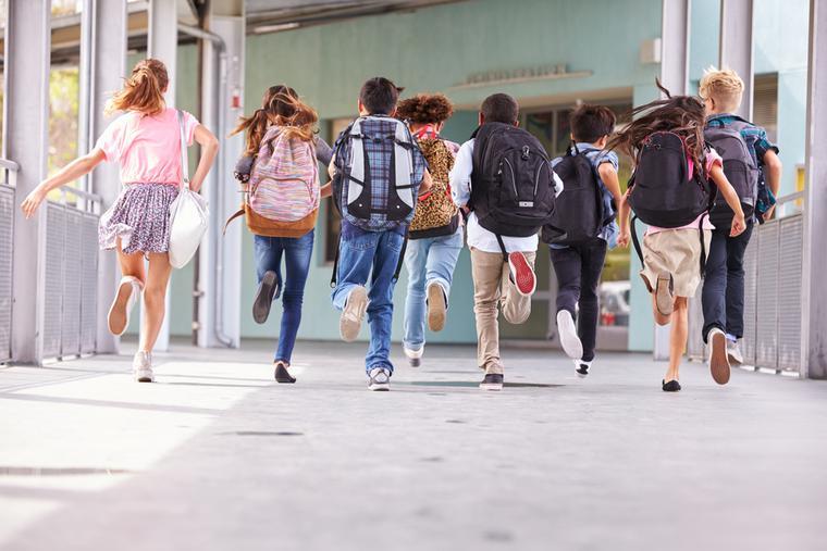 Elementary school kids run down the hallway at school.