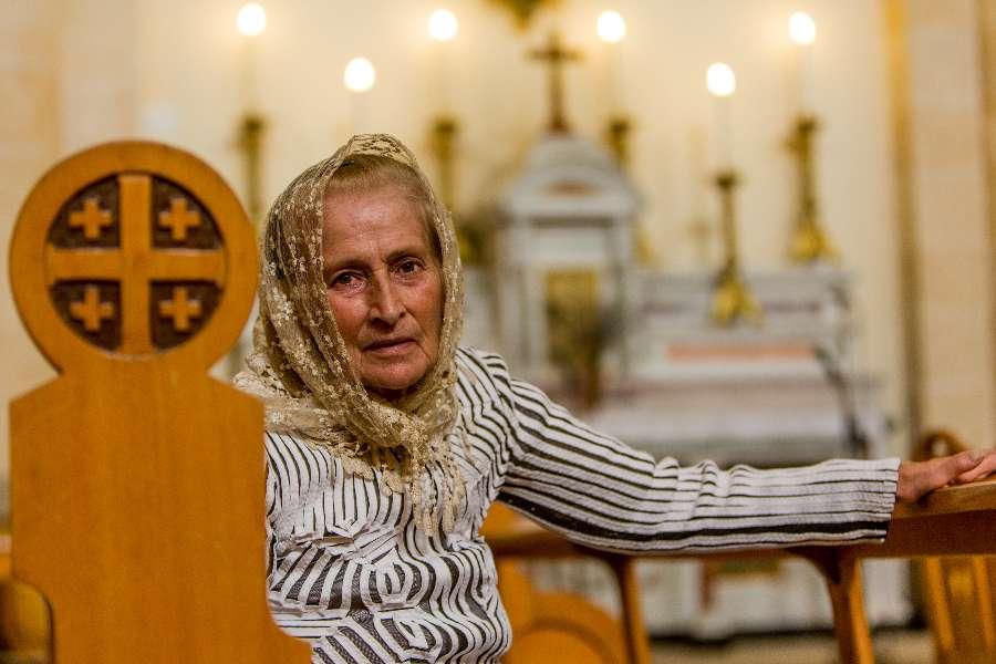 A Syrian woman sits inside a Catholic church.