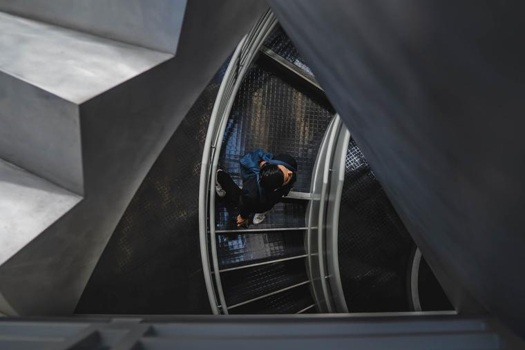 A student walks down a spiral staircase on way to class.
