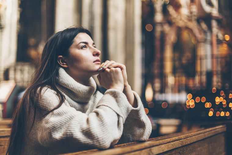 A young female parishioners sits praying at a Catholic church.