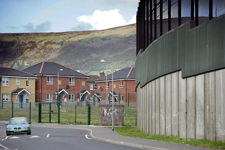 """The """"peace line,"""" a 25-foot high brick, steel and wire structure separating the city's nationalist and unionist communities, can be seen beside new homes in west Belfast, Northern Ireland, on April 29, 2008."""