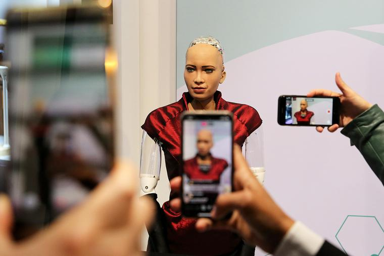 """Attendees take smartphone photographs of Hanson Robotics Inc.'s humanoid robot """"Sophia"""" on the opening day of the MWC Barcelona in Barcelona, Spain, on Feb. 25, 2019."""
