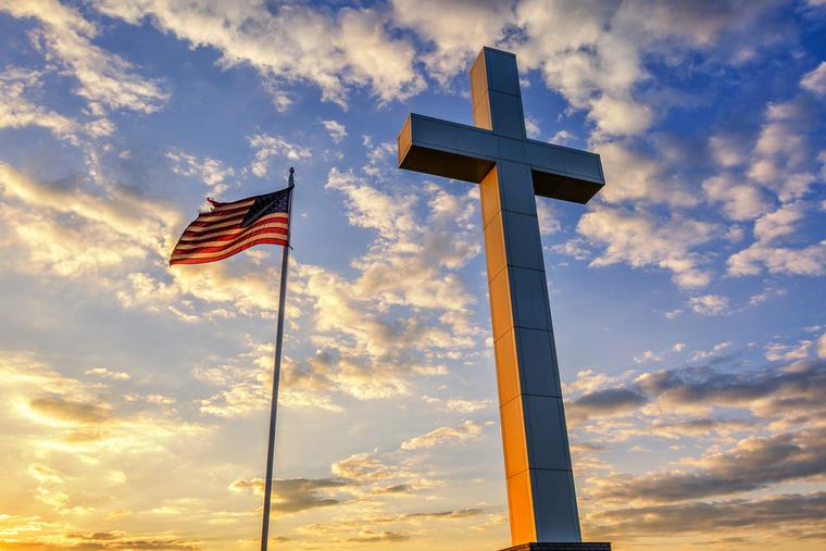 American flag waves next to a cross at sunset.