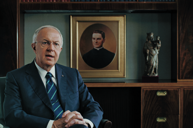 Supreme Knight Carl Anderson sits in his office with a picture of Blessed Michael McGivney behind him.