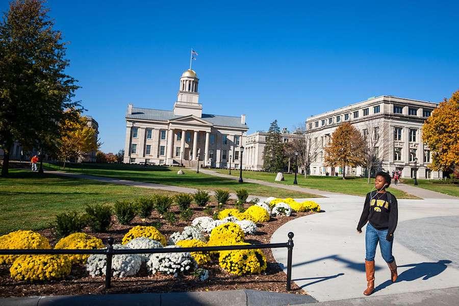 A student walks across campus at the University of Iowa, in Iowa City, Iowa.