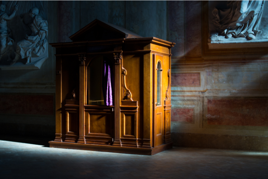 Confessional sits in a dark cathedral.
