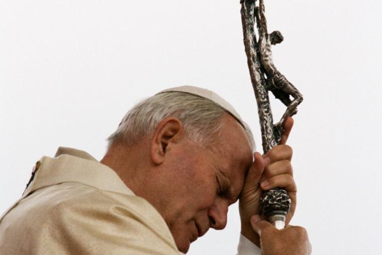 Pope John Paul II prays with his eyes closed while clutching his crosier bearing the crucifix on a visit to Colombia in July 1986.
