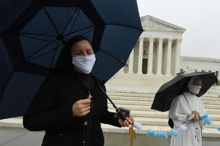 Little Sisters of the Poor supported by religious sisters from many orders convened in front of the United States Supreme Court wearing masks to pray the Rosary before the historic telephonic oral arguments in April, 2020.