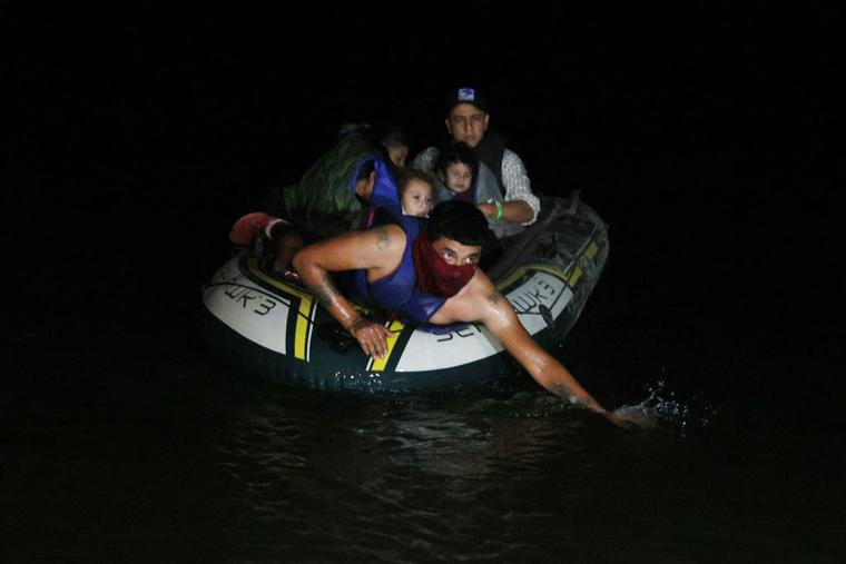 A smuggler paddles ashore a group of migrants entering the U.S. on the Rio Grande on March 30, 2021 in Roma, Texas. The group made up of individuals from Central America turned themselves into the U.S. Border Patrol after crossing as they seek asylum in the United States.