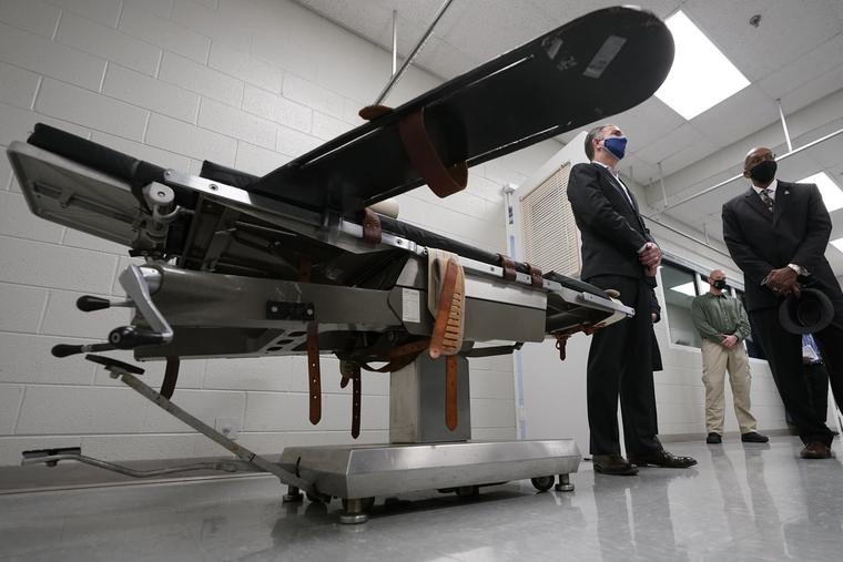 Gov. Ralph Northam, left, stands near a gurney with Greensville Correctional Center warden Larry Edmonds, right, at the Greensville Correctional Center prior to signing a bill abolishing the state's death penalty in Jarratt, Va., Wednesday, March 24, 2021.