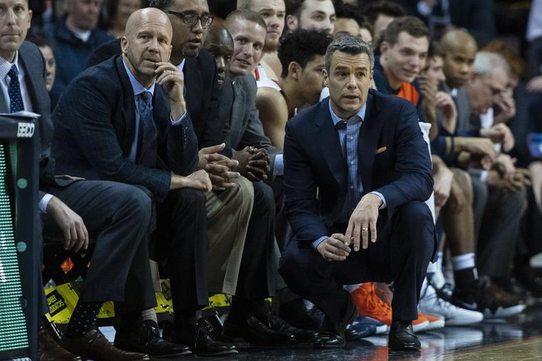 Virginia Cavaliers Assistant Coach Brad Soderberg (l) and Head Coach Tony Bennett (c) look on from the bench during the first half of the game between the Pittsburgh Panthers and the Virginia Cavaliers on March 2, 2019, at John Paul Jones Arena in Charlottesville, Virginia. The Cavs went on to win the 2019 NCAA National Championship.