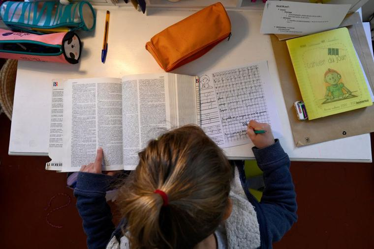 A child does his homework in Marseille, southern France, on April 6, 2021, as schools are closed in France as part of a lockdown to fight the spread of the COVID-19 pandemic.