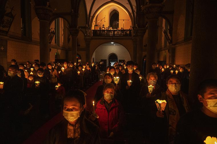 Chinese Catholics hold candles during the Easter Vigil Mass at a church in Beijing on April 3.
