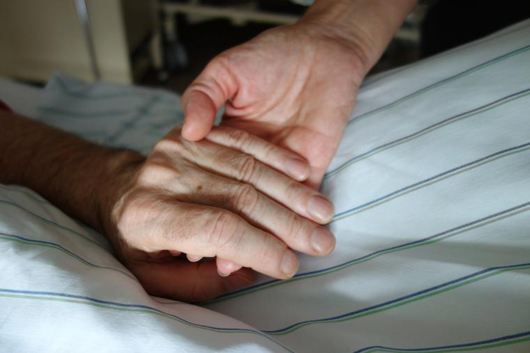 Nurse holding hand of a patient.