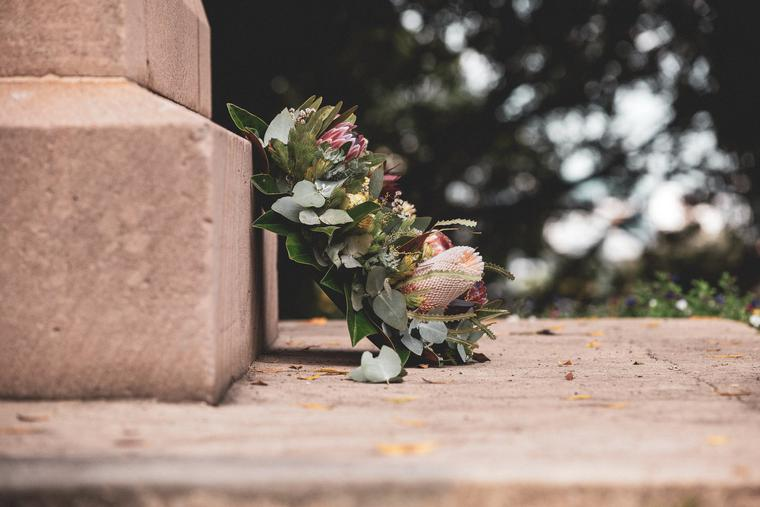 Flowers and wreath laid beside a headstone at a cemetery.