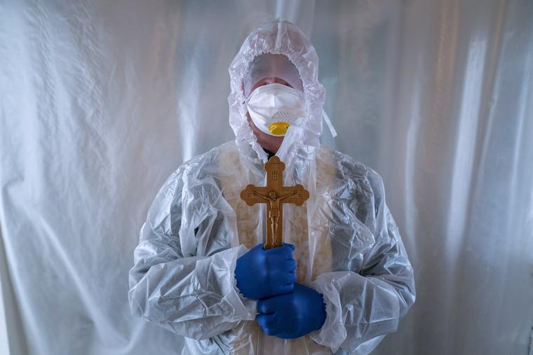 Father Stephan, a Ukrainian Greek Catholic Church priest, wearing a special suit to protect himself against coronavirus, stands, after visiting patients with COVID-19 at an intensive care unit of the emergency hospital in Lviv, Western Ukraine, Saturday, Jan. 9, 2021.