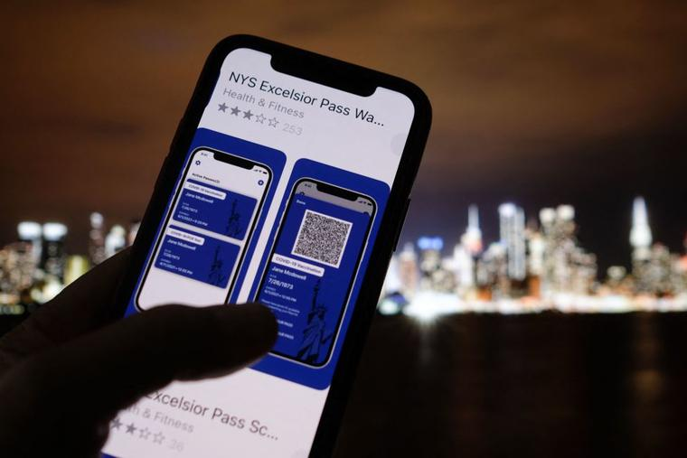 A debate has ensued over 'vaccine passports.' This illustration photo taken in Los Angeles on April 6 shows a person looking at the app for the New York State Excelsior Pass, which provides secure, digital proof of a COVID-19 vaccination, in front of a screen showing the New York skyline. As the United States' vaccination campaign accelerates, so-called vaccine passports are gaining traction despite political divisions and privacy and freedom concerns.