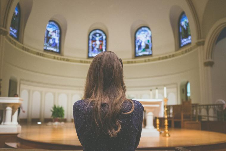 a young parishioner prays inside St. Thomas Catholic Church in Ann Arbor, Michigan.