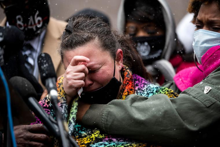 Naisha Wright (r) embraces Katie Wright (c), the mother of Daunte Wright, as she speaks during a news conference outside the Hennepin County Government Center on April 13 in Minneapolis. Daunte Wright was shot and killed by Brooklyn Center police officer Kimberly Potter on Sunday.