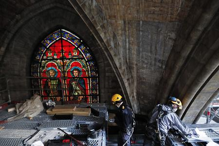 Technicians work under a vault of the Notre-Dame de Paris Cathedral ahead of a visit of French President Macron two years after the blaze that collapsed the spire and destroyed much of the roof on April 15, 2021. The actual restoration work has yet to begin as time up until now has been spent on securing the building, and the full restoration works should begin early next year.