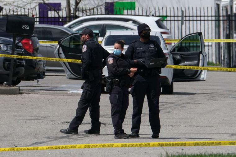 Police officers stand guard outside the site of a mass shooting at a FedEx facility in Indianapolis, Indiana on April 16, 2021.