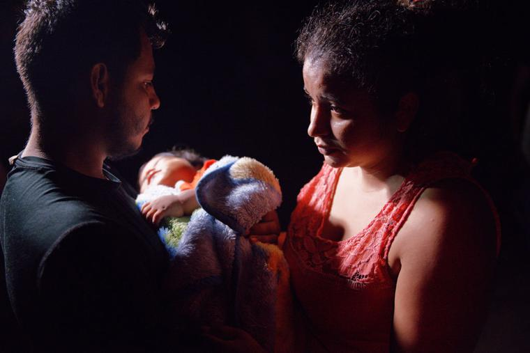 Honduran parents hold their sleeping boy after crossing the Rio Grande from Mexico on April 15, 2021 in Roma, Texas.