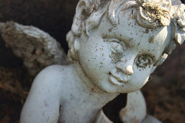 A statue of an angel marking the grave of a baby.