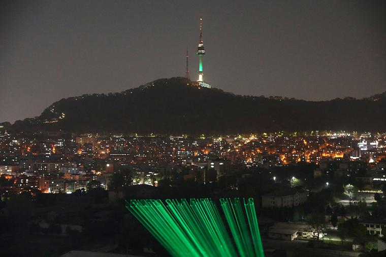 """Greenpeace activists project a laser message saying """"Leaders Save Earth, Save Us"""" Wednesday in Seoul, South Korea. President Biden has invited 40 world leaders, including Pope Francis, to participate in the Leaders Summit on Climate and is hoping to reach deals with some of the world's largest greenhouse gas emitters."""