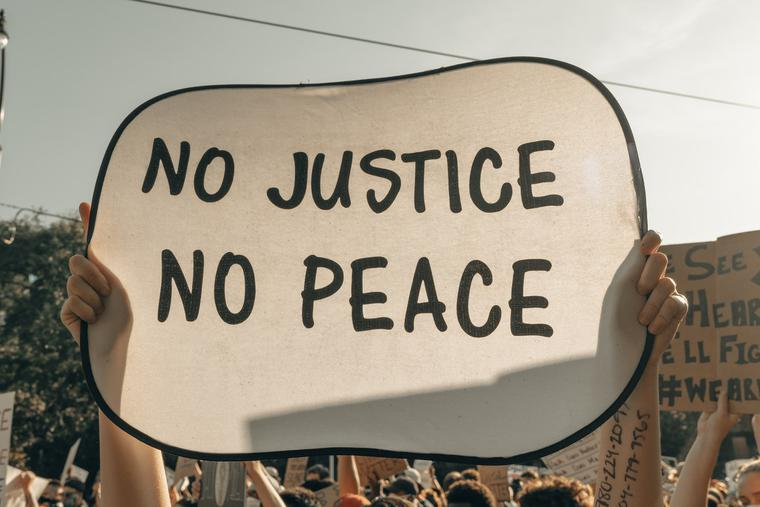 Protesters in Minneapolis hold signs before the verdict in the case against Derek Chauvin was decided.