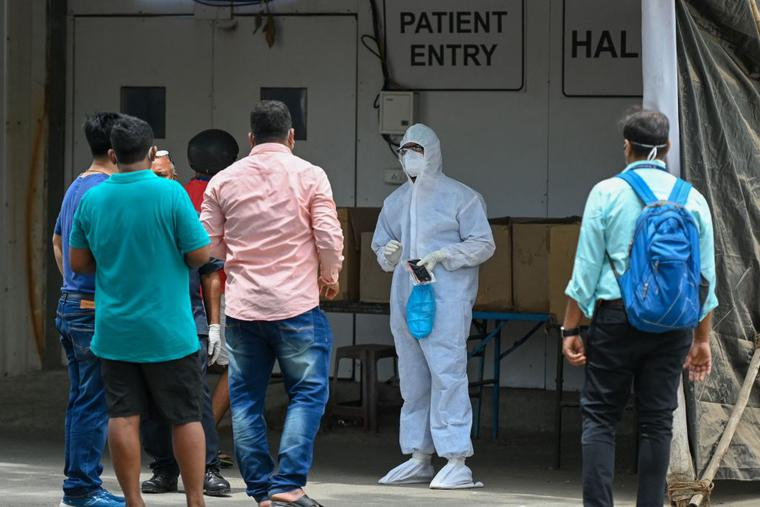 A health worker wearing Personal Protective Equipment (PPE) gear speaks with family members outside a recovery center to treat COVID-19  patients, in Mumbai, India, on April 22. Coronavirus infections are currently spiking there.