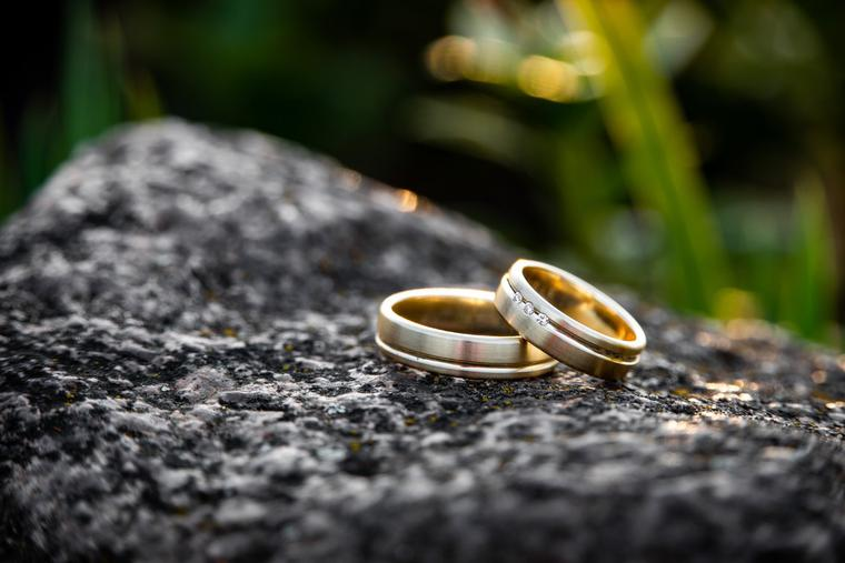 A photographer captures a couple's wedding rings on the day of marriage.