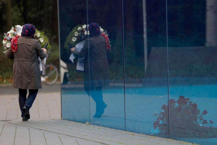 """A woman carries a wreath as she arrives at a ceremony to pay respect at the T4 Memorial and Information Point for the Victims of the Nazi Euthanasia Program in Berlin on Sept. 4, 2020. Administrators and doctors of the Nazi regime organized the mass murder of people with intellectual disabilities and mental illness. The annihilation of more than 70,000 patients in institutions was later named """"Aktion T4"""" after the address of the program's headquarters, Tiergartenstrasse 4."""
