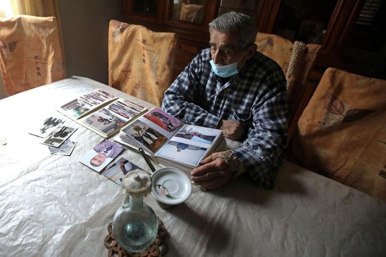 Jean Assaf, an 80-year-old retired police officer who earns a monthly pension worth around $180, down from $1,400 before the crisis, looks at an old photo album at his home in Beirut's Mar Mikhael district on March 24. Lebanon is in the grips of its worst economic crisis since the 1975-1990 civil war, with more than half of its population living in poverty.