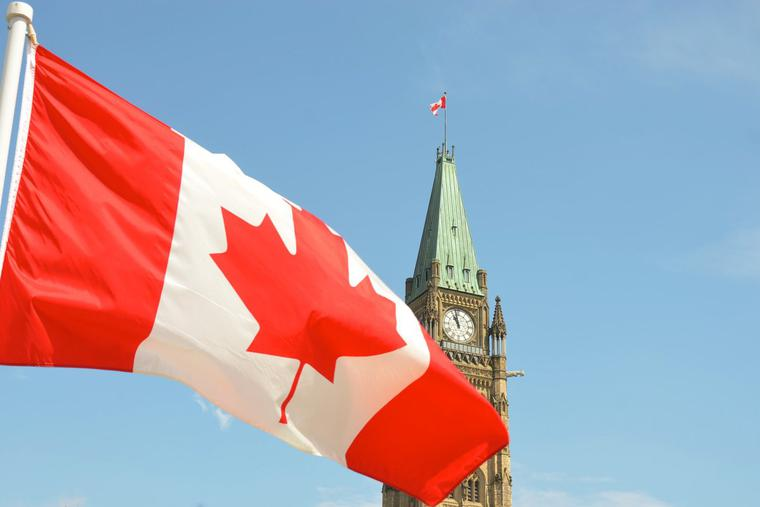 Canadian flag waving in front of the Parliament Building on Parliament Hill in Ottawa.