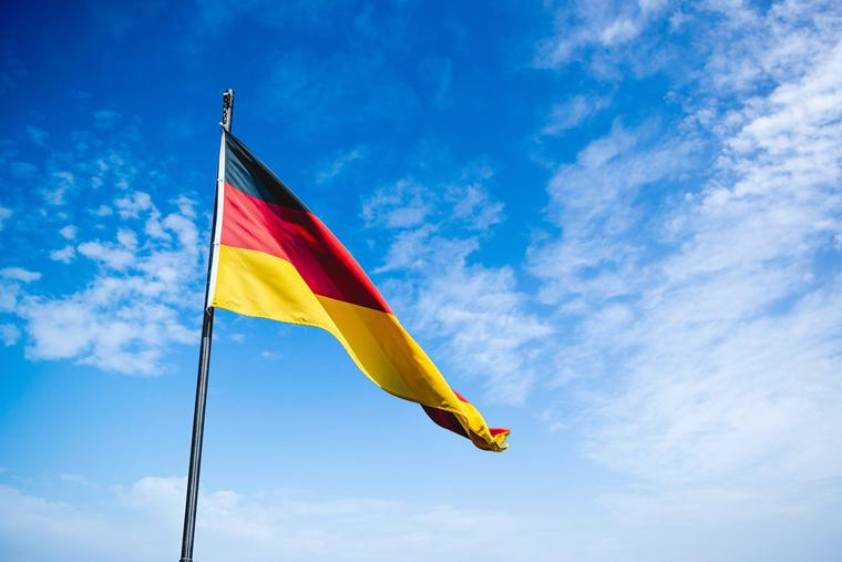 Flag of Germany waves in the breeze on a clear day in Berlin.