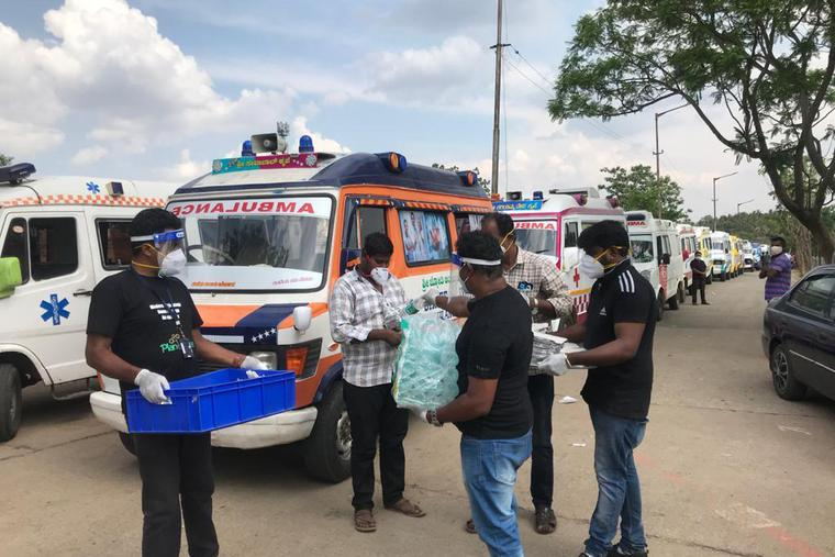Ambulance drivers being given food packets from 'Mother's Kitchen.'