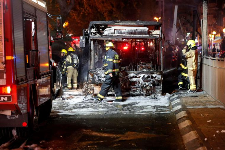 Israeli firefighters check out a burnt bus in the Israeli town of Holon near Tel Aviv, on May 11, 2021, after rockets are launched towards Israel from the Gaza Strip controlled by the Palestinian Hamas movement.