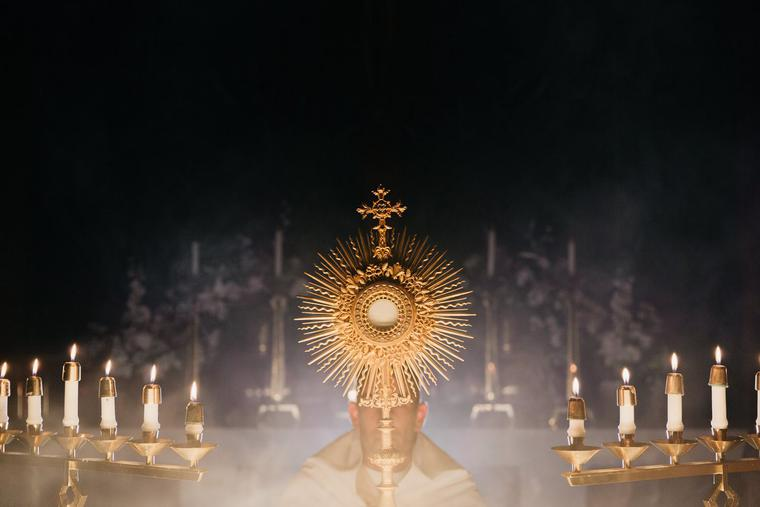A priest carries the monstrance containing the Eucharist during a cande-lit procession.
