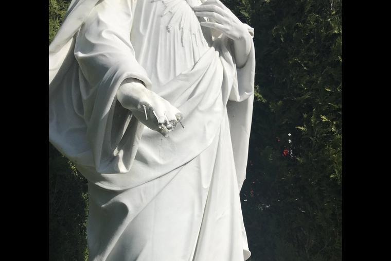 Close-up of the hand of Jesus on a statute vandalized at St. Thomas More Catholic Church in Narragansett, R.I.